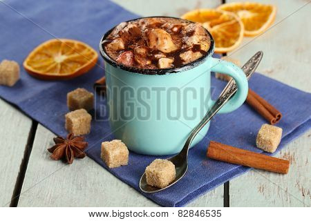Cup of hot coffee with marshmallow on napkin with lump sugar, cinnamon, star anise and dried orange on color wooden table background