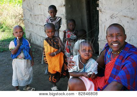 Maasai Family In Doorway Of His Home, Father And Children.
