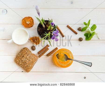 milk, wheat bread and orange jam on a white wooden table