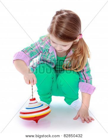 pretty little girl playing with a spinning top.
