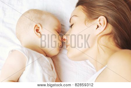 Baby And Mother Sleeping Together On The Bed