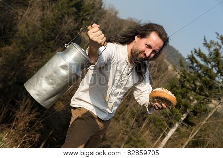 Long-haired Grower Offering A Milk Churn And Bread