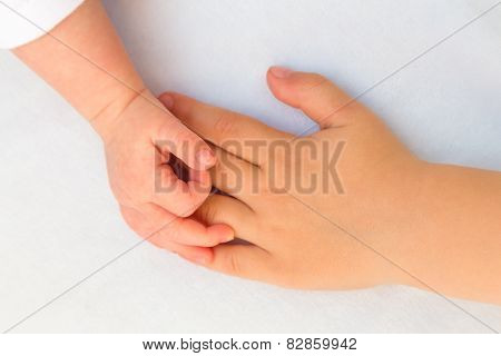 Touching hands of little girl and baby