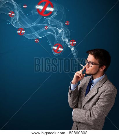 Attractive young man smoking dangerous cigarette with no smoking signs