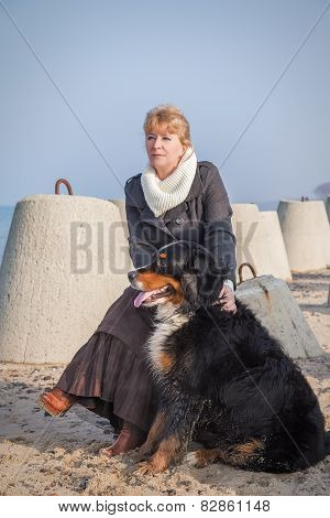 Dog And Woman Sitting Near Sea