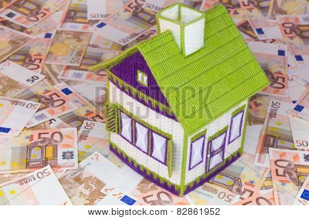 Embroidered house on euro notes