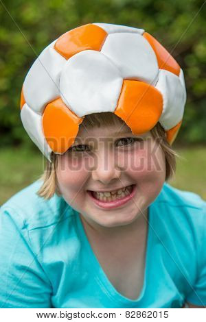 Young girl wearing leather football on head