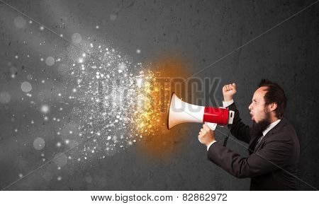 Guy shouting into megaphone and glowing energy particles explode concept