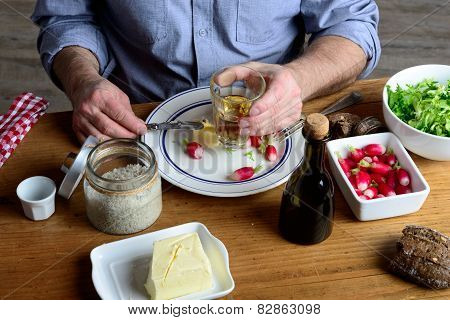 A Man Eat Radishes With Butter And Drink Cider