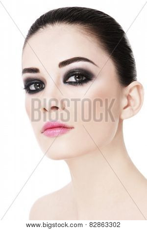 Portrait of young beautiful woman with smokey eyes over white background