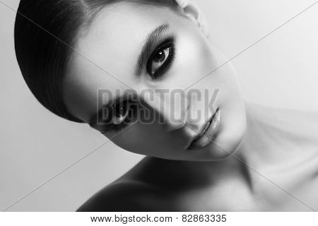 Close-up horizontal black and white portrait of young beautiful woman with smokey eyes