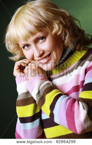 Mature blonde woman posing wearing a colorful sweater