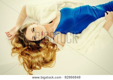 Stunning young woman posing in fashionable dress and mink fur jacket. Luxury, rich lifestyle. Fashion shot. Isolated over white background.