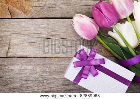 Fresh tulips bouquet and gift box on wooden table with copy space
