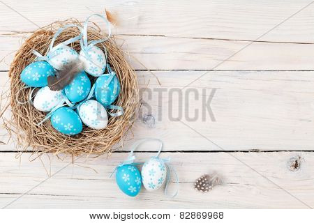 Easter background with blue and white eggs in nest over white wood. Top view with copy space