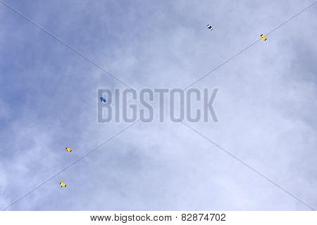 Five parachute against the sky.
