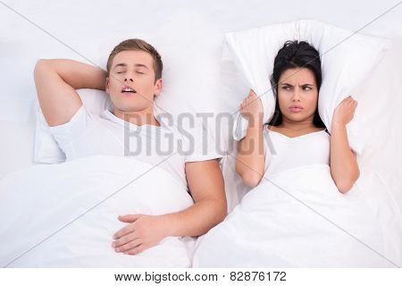 Angry woman and snoring man in bed