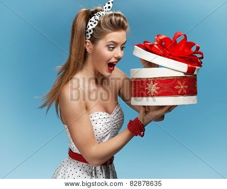 Excited birthday girl opening surprise gift with a look of amazement and shock