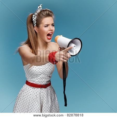 Angry pin-up girl shouting into a megaphone, mouthpiece, speaking trumpet
