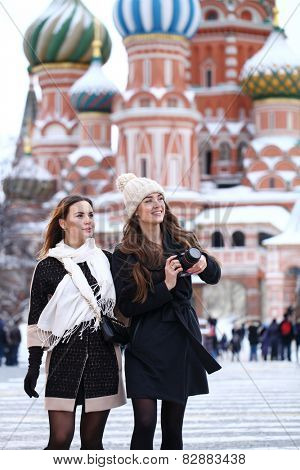 Two girls tourists are photographed in Moscow (Russia) winter 2015