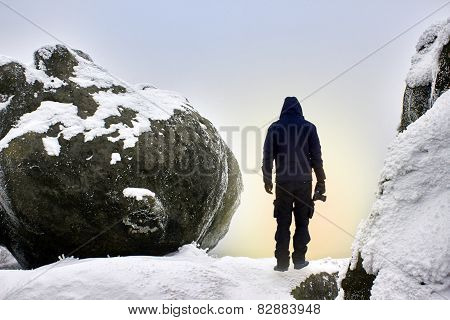 Silhouette of man on the snowy mountain at sunrise.