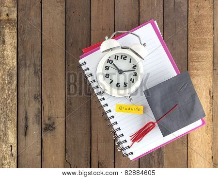 Graduation Cap And Clock  On Notebook