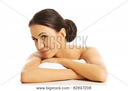 Serene woman lying on a rolled towel with folded arms.