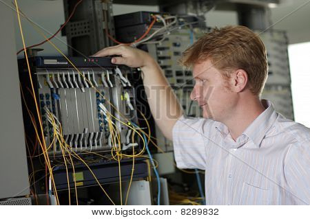 Telecom Engineer Looks On Multiplexer