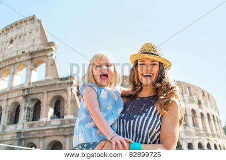 Portrait Of Happy Mother And Baby Girl In Front Of Colosseum In Rome, Italy