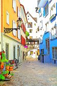 picture of quaint  - Quaint Austrian town with cobblestone street and colorful storefronts - JPG