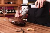 stock photo of wine cellar  - Confident male sommelier pouring wine to decanter while standing near the wine shelf - JPG