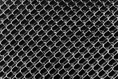 stock photo of chain link fence  - An abstract background image of a color inverted chain link fence processed in black and white - JPG