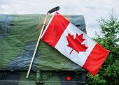 stock photo of military personnel  - A close up of a Canadian flag attached to a hockey stick hanging on the side of a Canadian Armed Forces military personnel transport truck showing pride to honor Canadian national war heroes - JPG