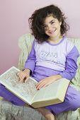 foto of ten years old  - Ten year old girl in pajamas and old encyclopedia - JPG
