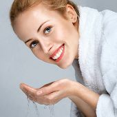 stock photo of water jet  - Young woman washing face with clean water - JPG
