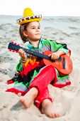 stock photo of sombrero  - Toned photo of Little happy smiling boy plays his guitar wearing a yellow sombrero - JPG