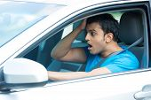 pic of outrageous  - Closeup portrait dumbstruck dumbfounded young sitting man in blue shirt wide open eyes and mouth by drivers in front of him isolated city street background - JPG