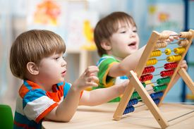 picture of playground school  - happy kids boys playing with abacus toy indoors - JPG