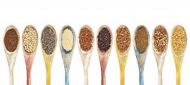 stock photo of sorghum  - a collection of gluten free grains and seeds on isolated wooden spoons  - JPG