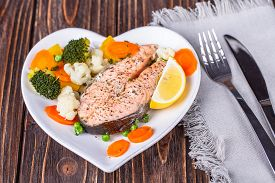 foto of steam  - Steamed salmon with vegetables on plate in the form of heart on wooden background  - JPG