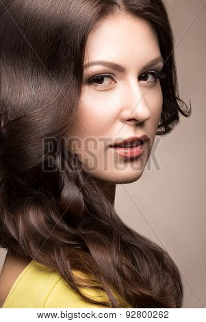 Beautiful woman in a light dress with evening makeup, pale lips and curls. Beauty face.