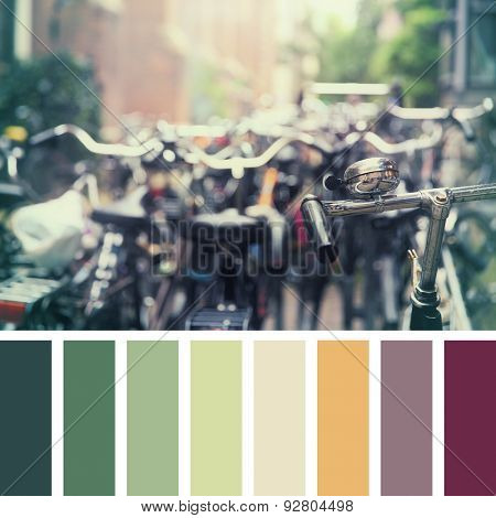 Numerous bikes parked in an Amsterdam street, with intentional shallow focus on the front handlebar. In a colour palette with complimentary colour swatches.