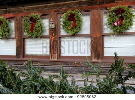 Holiday wreaths on rustic wood windows