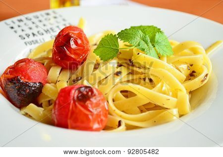 Tagliatelle with cherry tomatoes and mint on the white plate