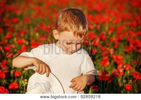 Cute Little Boy With Poppy Flower On Poppy Field On Summer Day