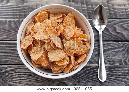 Bowl Of Corn Flakes And Spoon Lie On A Wooden Surface. Healthy Breakfast.