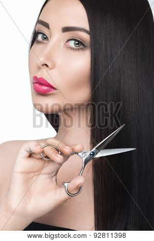 Beautiful brunette girl with a perfectly smooth hair, scissors and classic make-up. Beauty face.