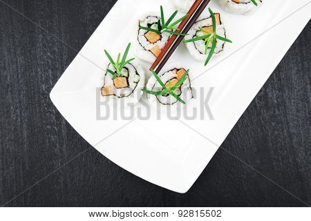 Japanese Cuisine - California Roll made of Salmon, Cream Cheese and Avocado inside. Served with wasabi and ginger . on long white plate over black table