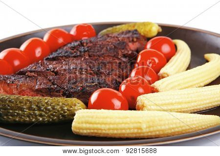 roast beef with tomatoes and corns on dark plate