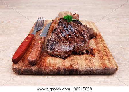 barbecued beef fillet on wooden plate with cutlery over table